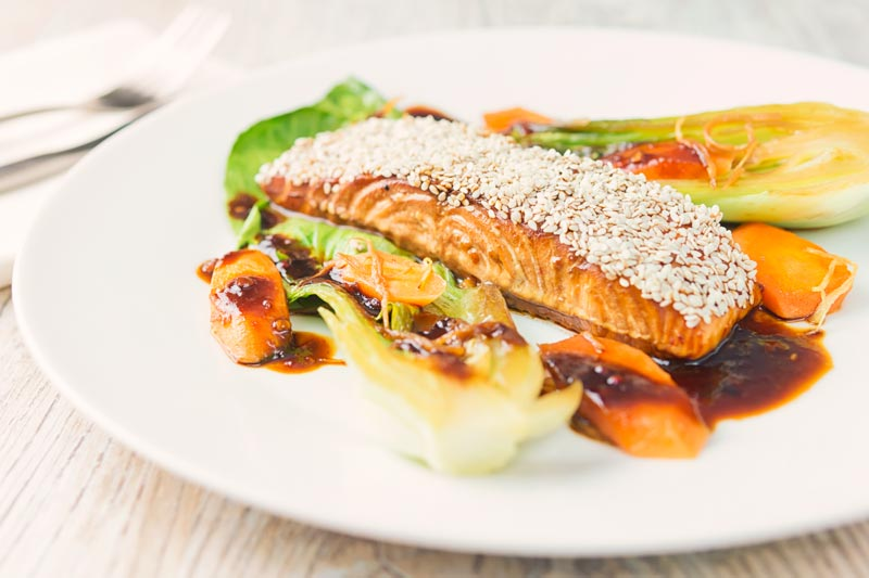 Landscape image of a sesame salmon fillet served with ginger bok choi and carrots on a white plate