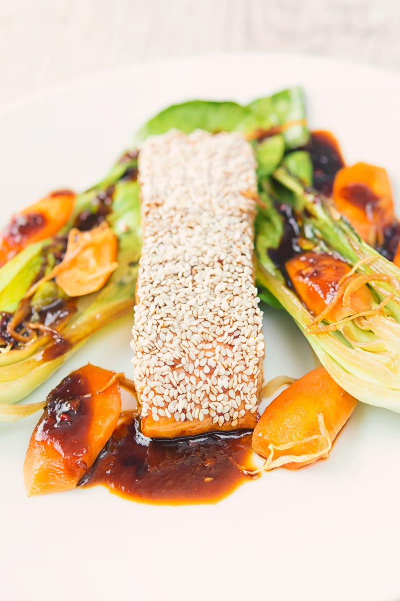 Close up portrait image of a sesame salmon fillet served with ginger bok choi and carrots on a white plate