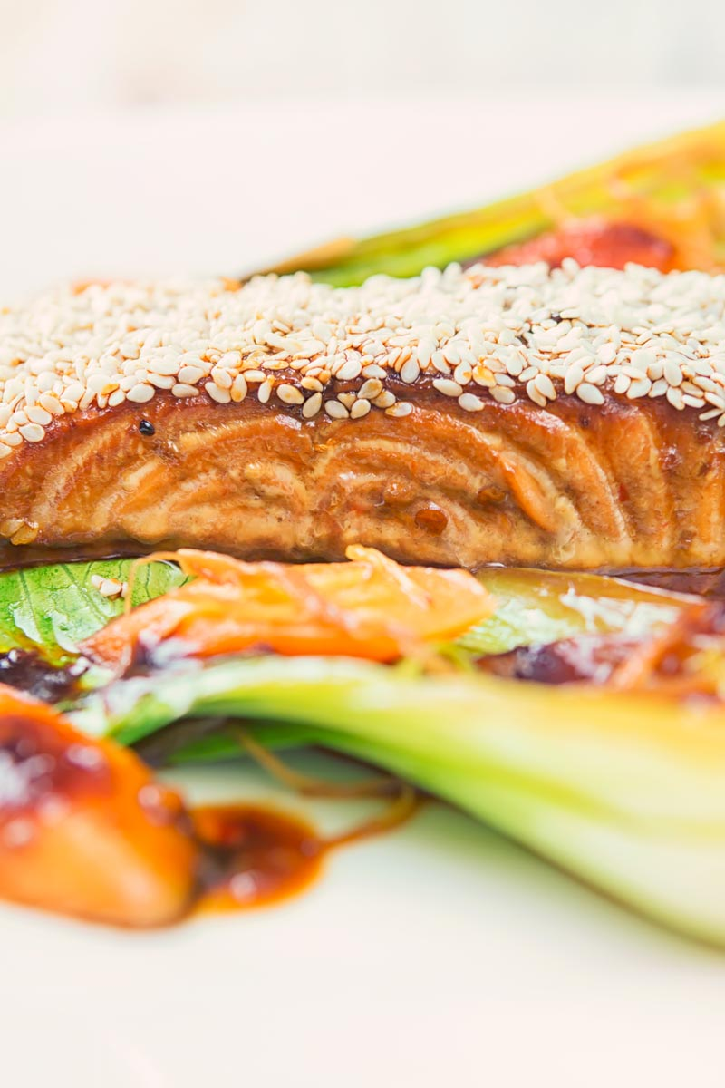 Portrait close up abstract image of a sesame salmon fillet served with ginger bok choi and carrots on a white plate