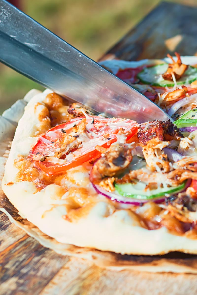 Tall image of a grilled pizza featuring tomato, red onion, cucumber and bbq chicken being cut on a wooden chopping board
