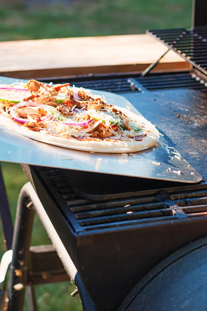 Tall image of a raw pizza being transferred to to a pizza steel on a bbq to become a grilled pizza