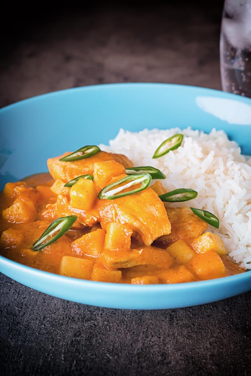Tall image of a colourful fruity pineapple chicken curry served in a blue bowl with white basmati rice set against a dark backdrop