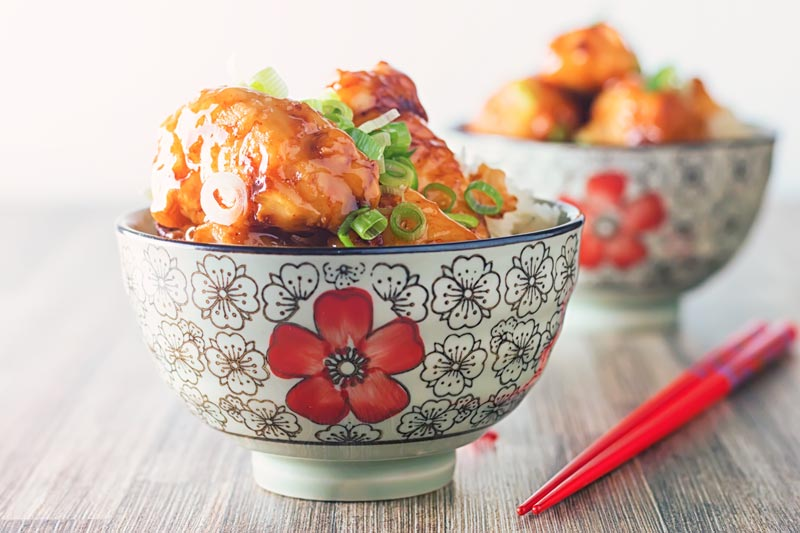 Landscape image of Chicken with Honey and Soy with a shiny glaze served in an Asian style bowl decorated with a red flower set against a white backdrop