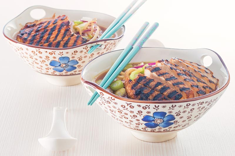 Landscape image of a spicy pork ramen noodle soup served in an Asian style bowl decorated with a blue flower