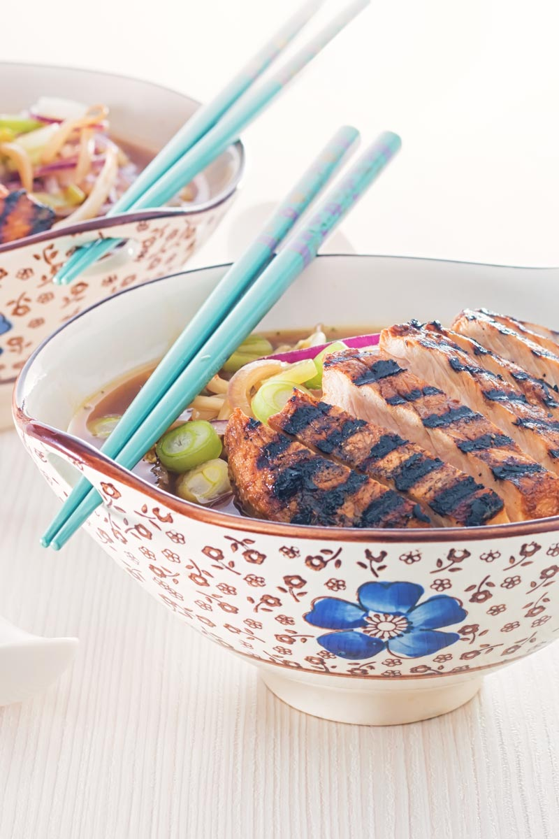 Portrait image of a spicy pork ramen noodle soup served in an Asian style bowl decorated with a blue flower