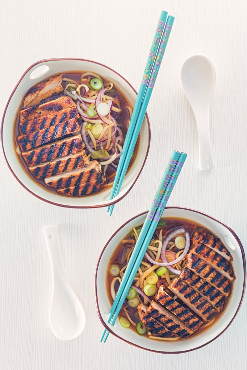 Overhead portrait image of a spicy pork ramen noodle soup served in two bowls