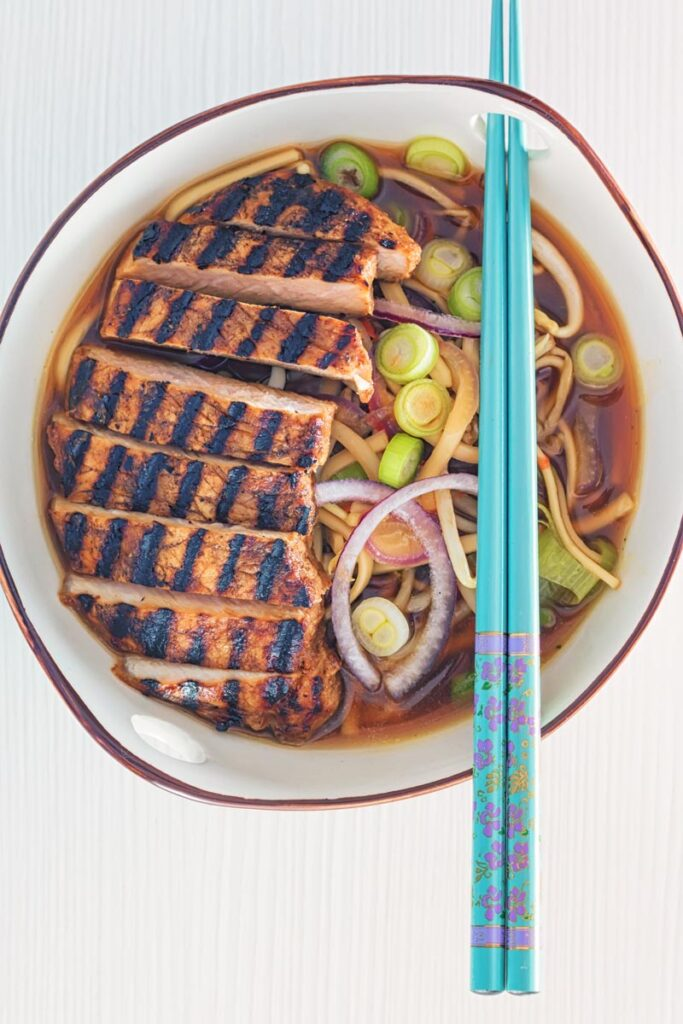 Overhead portrait image of a spicy pork ramen noodle soup served in a bowl with turquoise chopsticks