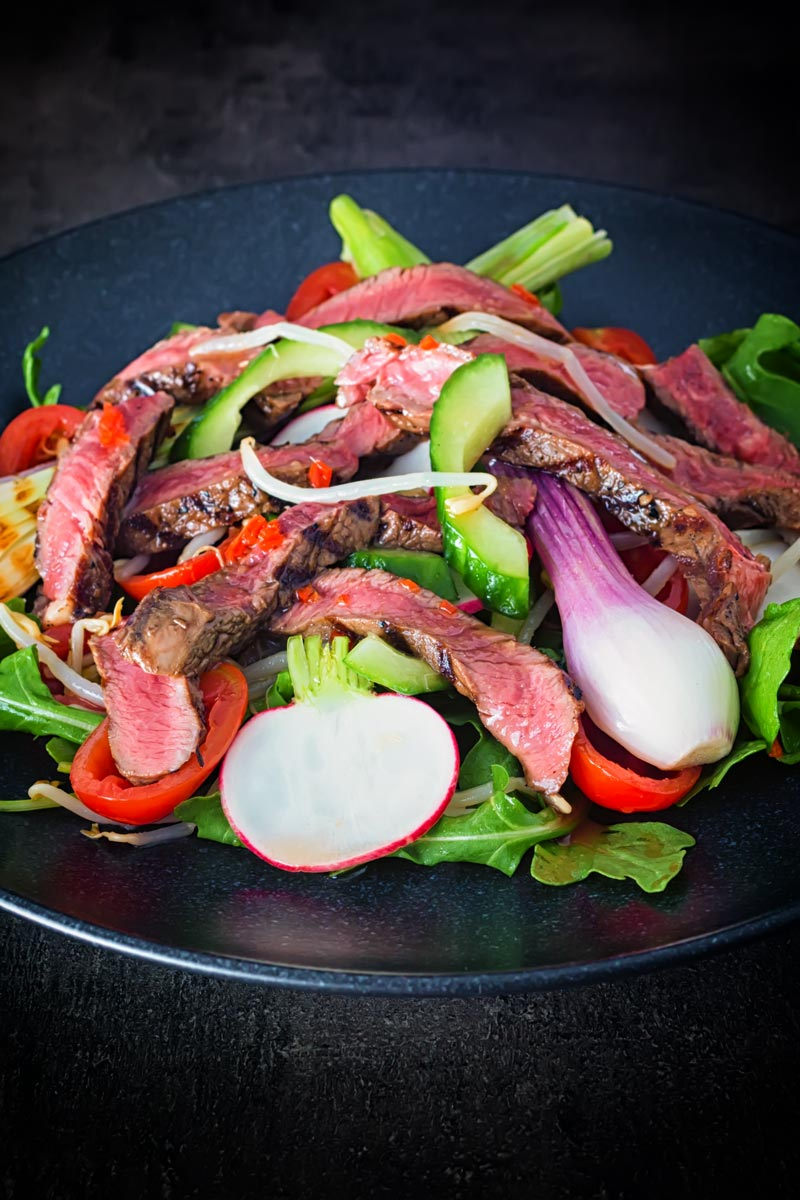 Portrait image of Thai beef salad featuring rare steak, grilled purple spring onions and radishes