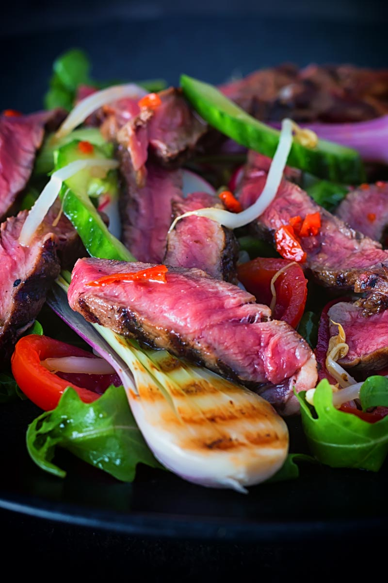 Portrait close up image of Thai beef salad featuring rare steak, grilled purple spring onions and radishes