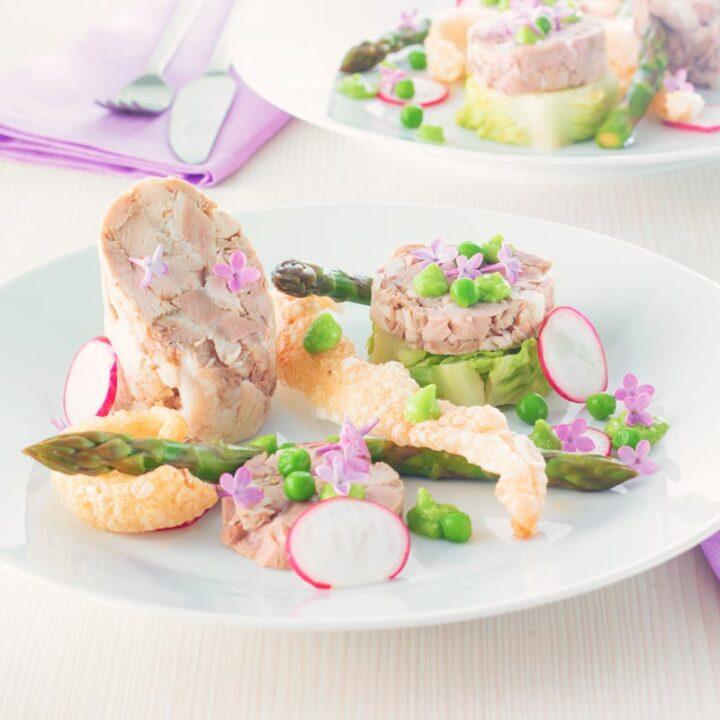 Square image of a spring ham hock salad, featuring pressed ham hock, asparagus, peas, lettuce, radish, and puffed pork crackling.