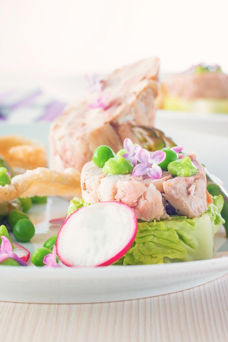 Portrait close up image of a spring ham hock salad, featuring pressed ham hock, asparagus, peas, lettuce, radish, and puffed pork crackling.