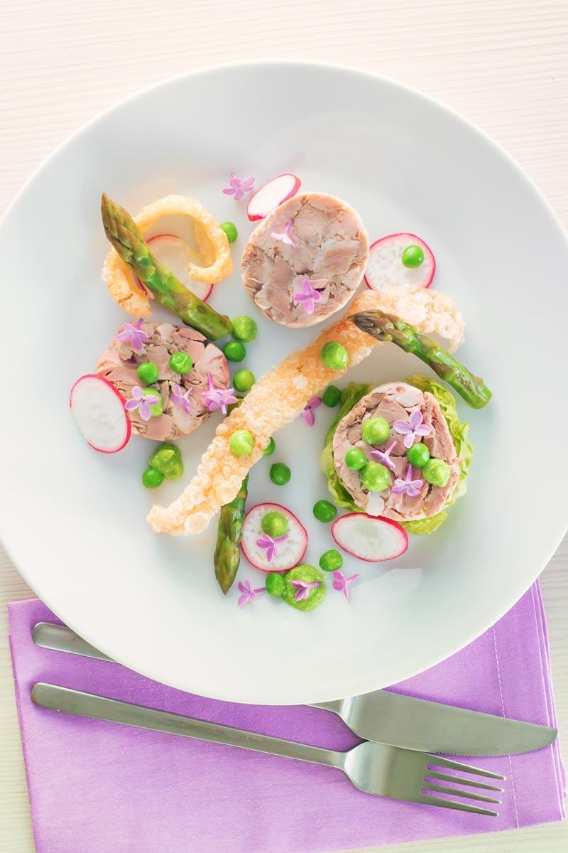 Portrait overhead image of a spring ham hock salad, featuring pressed ham hock, asparagus, peas, lettuce, radish, and puffed pork crackling.