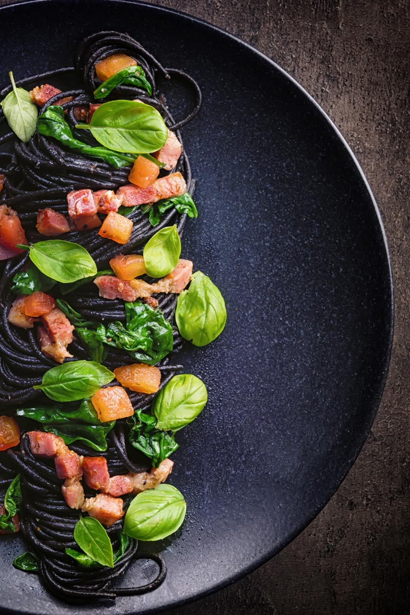Tall over head image of black squid ink pasta with bacon, spinach and basil plated elegantly on a black plate against a dark backdrop
