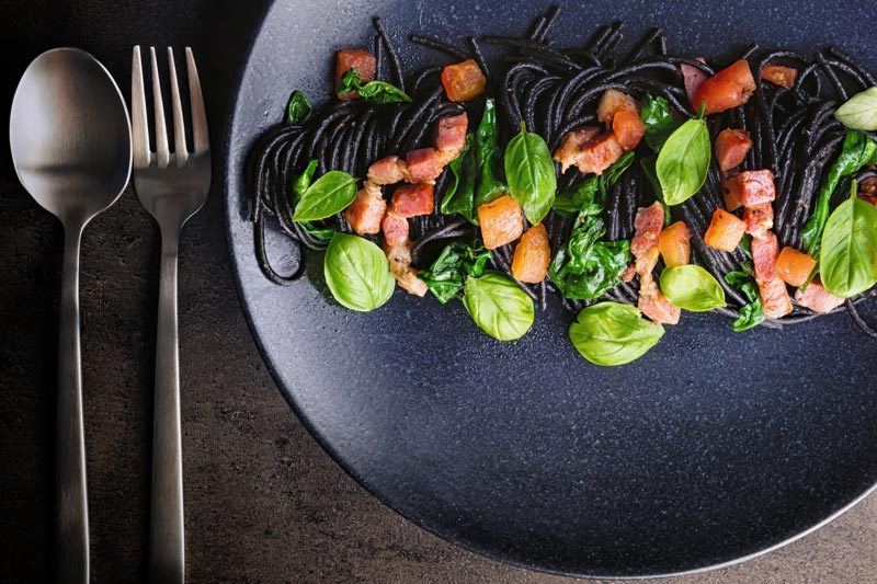 Landscape over head image of black squid ink pasta with bacon, spinach and basil plated elegantly on a black plate against a dark backdrop with a fork and spoon