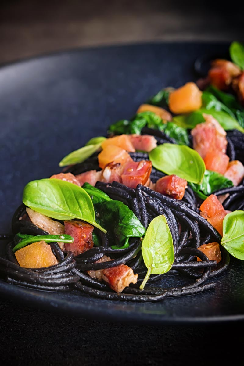 Portrait close up image of black squid ink pasta with bacon, spinach and basil plated elegantly on a black plate against a dark backdrop with a fork and spoon