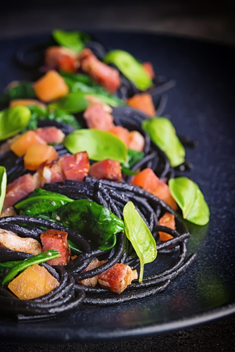 Portrait image of black squid ink pasta with bacon, spinach and basil plated elegantly on a black plate against a dark backdrop with a fork and spoon