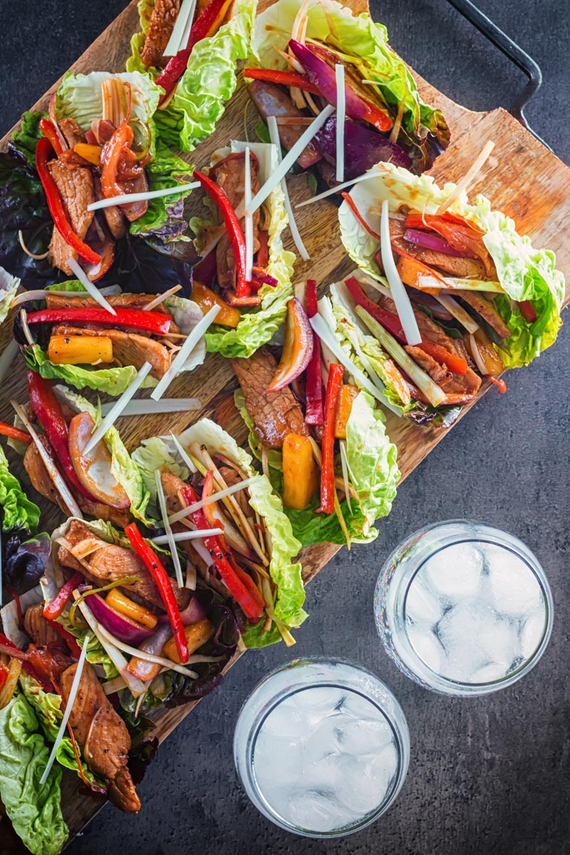 Tall overhead image of pineapple and pork lettuce wraps on a chopping board against a dark backdrop