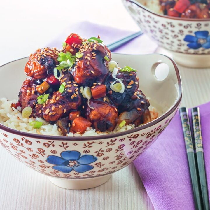 Square image of sweet and sour pork balls in an Asian style bowl decorated with a blue flower against a light backdrop
