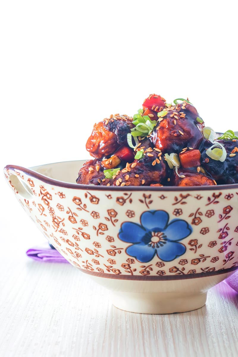 Portrait image of sweet and sour pork balls in an Asian style bowl decorated with a blue flower against a light backdrop