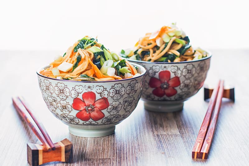 Landscape image of two bowls with Asian patterns and chopsticks containing sweet and sour Stir Fried Noodles