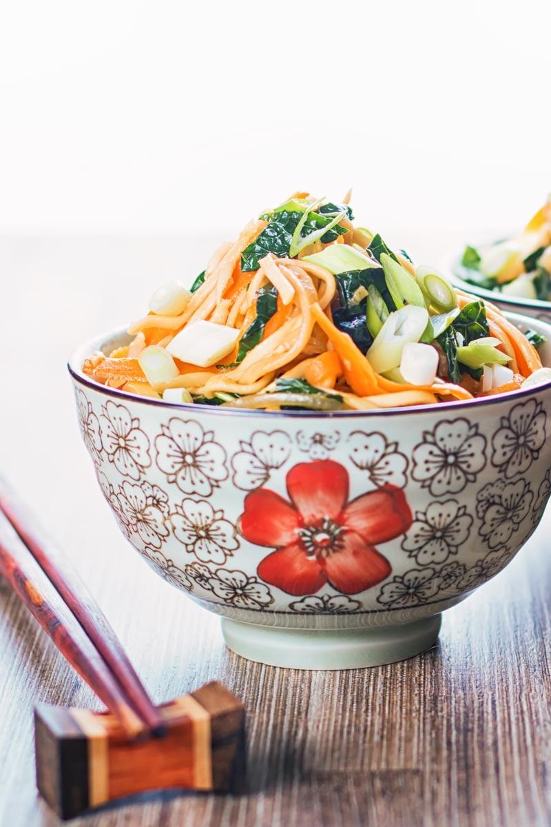Portrait image of a bowl with Asian patterns and chopsticks containing sweet and sour Stir Fried Noodles