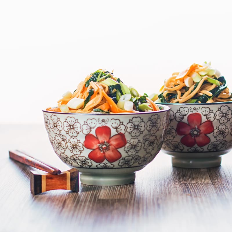Square image of two bowls with Asian patterns and chopsticks containing sweet and sour Stir Fried Noodles