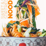 Close up portrait image of a bowl with Asian patterns with sweet and sour Stir Fried Noodles being lifted with chopsticks with text