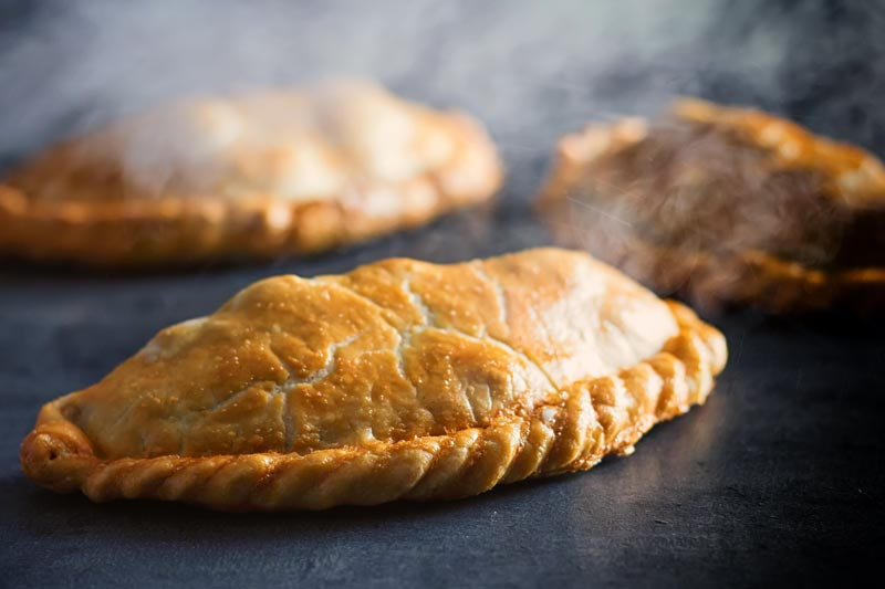 Landscape image of a traditional Cornish Pasty against a steamy dark back drop