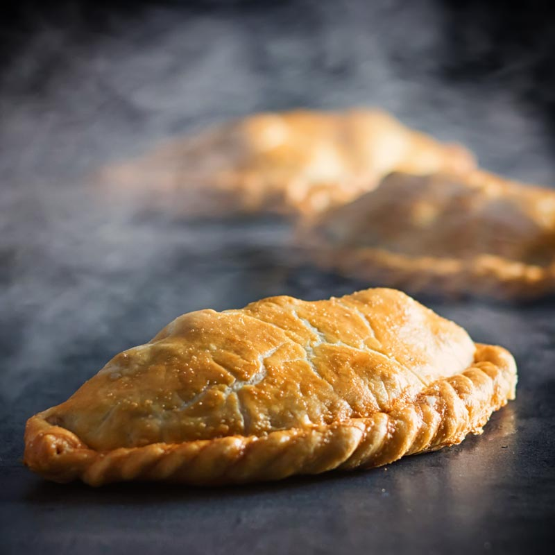 Square image of a traditional Cornish Pasty against a steamy dark back drop