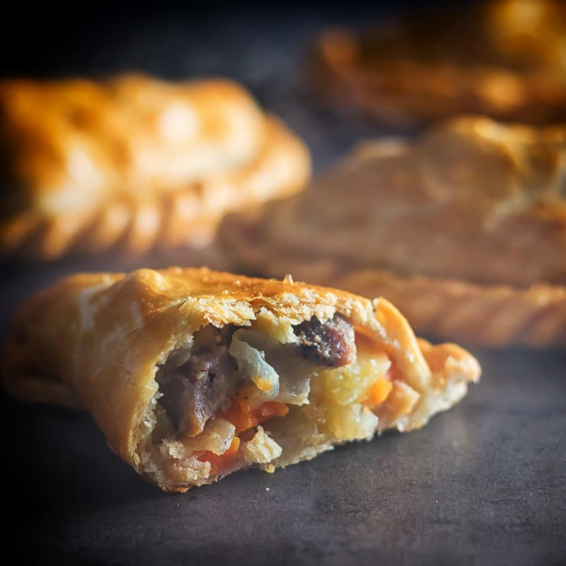 Square image of half of a traditional Cornish Pasty showing filling against a steamy dark back drop