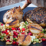 Portrait image of zaatar chicken legs served with giant couscous, pomegranate seeds and roasted shallots served on a black plate with text