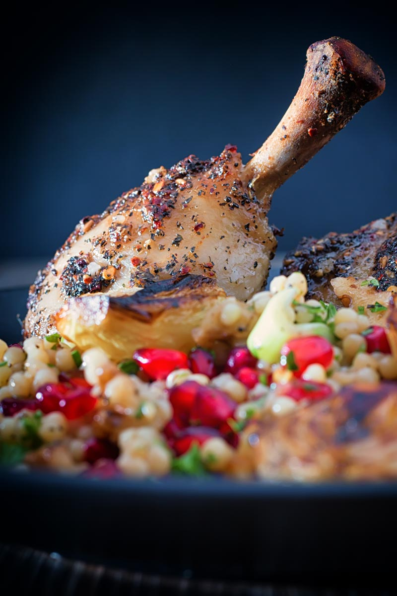 Close up portrait image of zaatar chicken legs served with giant couscous, pomegranate seeds