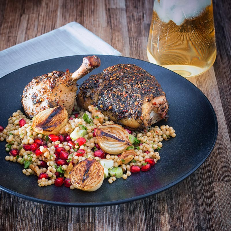 Square image of zaatar chicken legs served with giant couscous, pomegranate seeds and roasted shallots served on a black plate