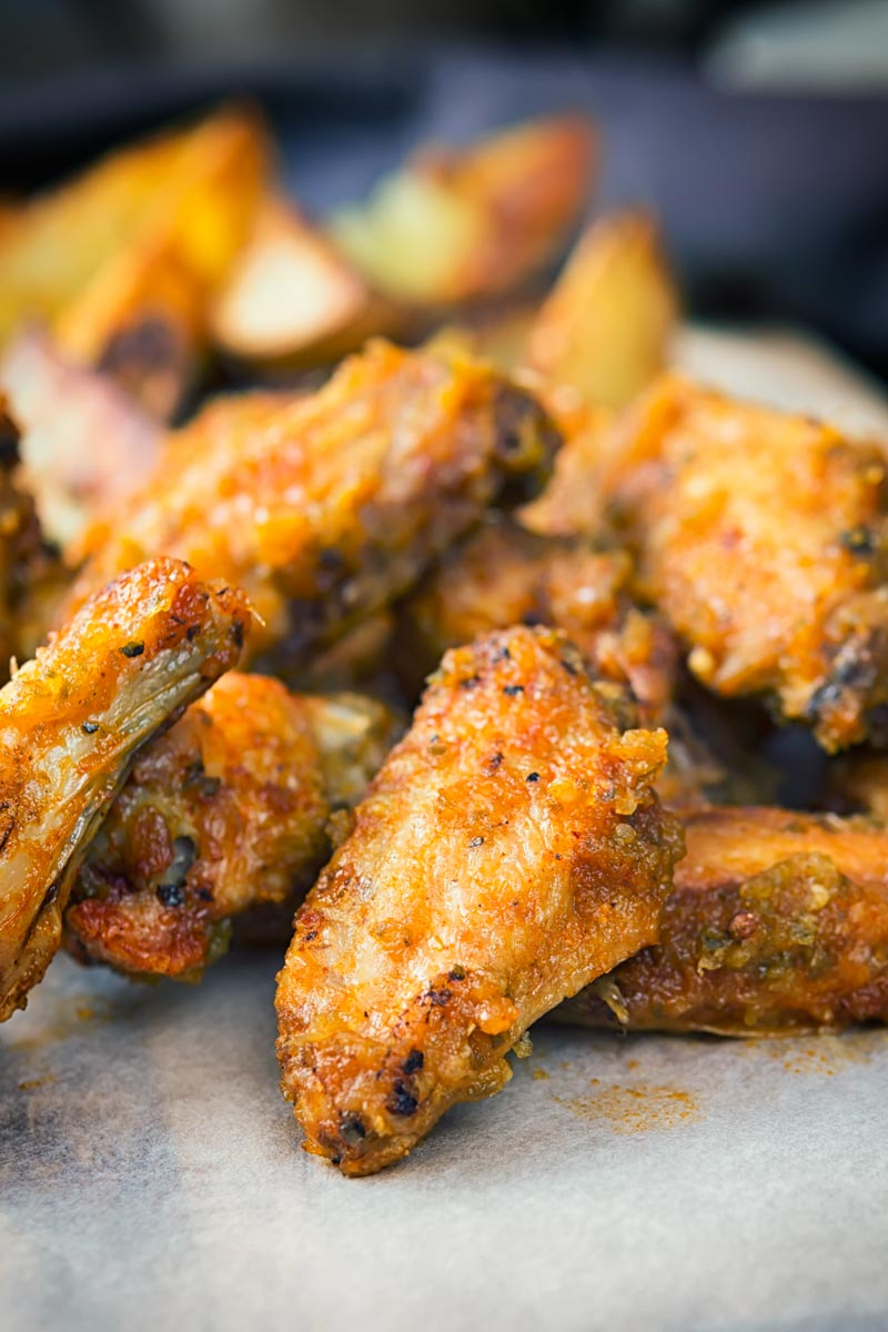 Portrait close up image of air fryer chicken wings served with potato wedges served on a wooden chopping board