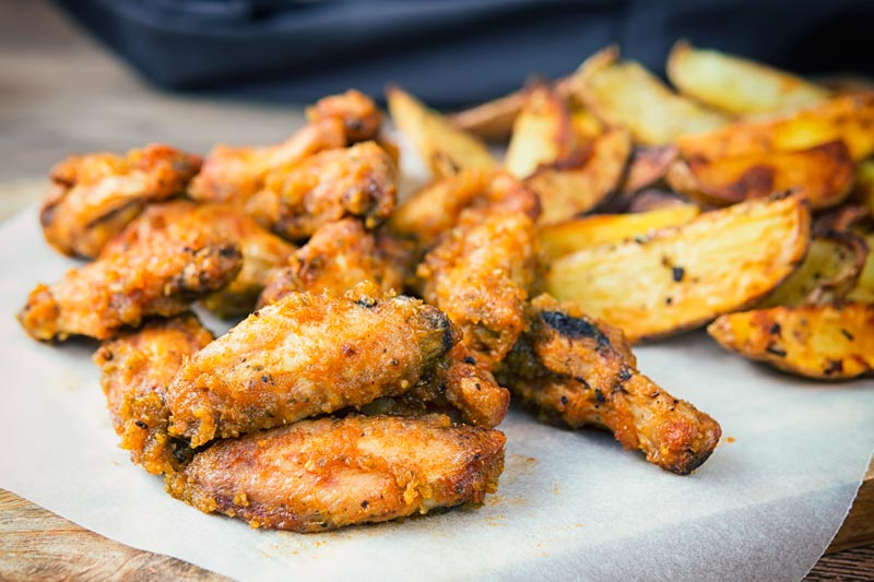 Landscape image of air fryer chicken wings served with potato wedges served on a wooden chopping board