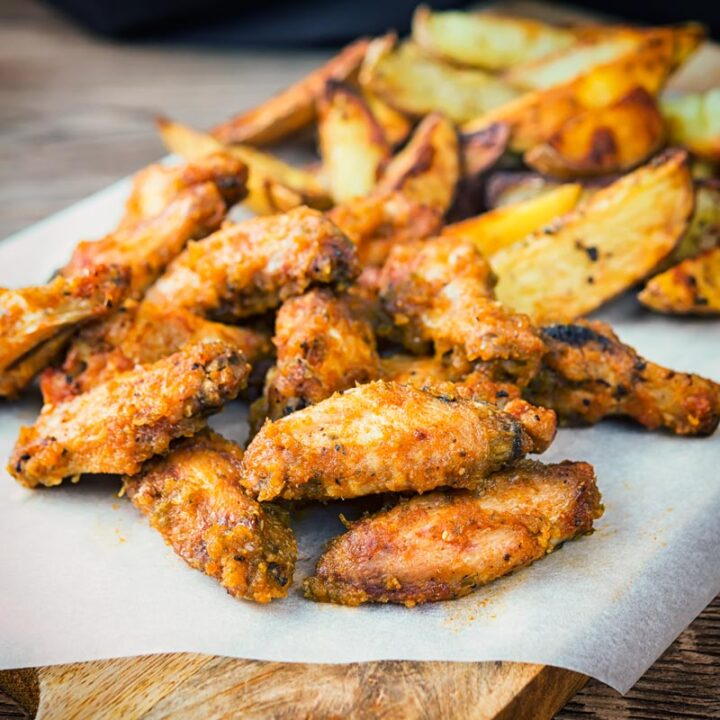 Square image of air fryer chicken wings served with potato wedges served on a wooden chopping board