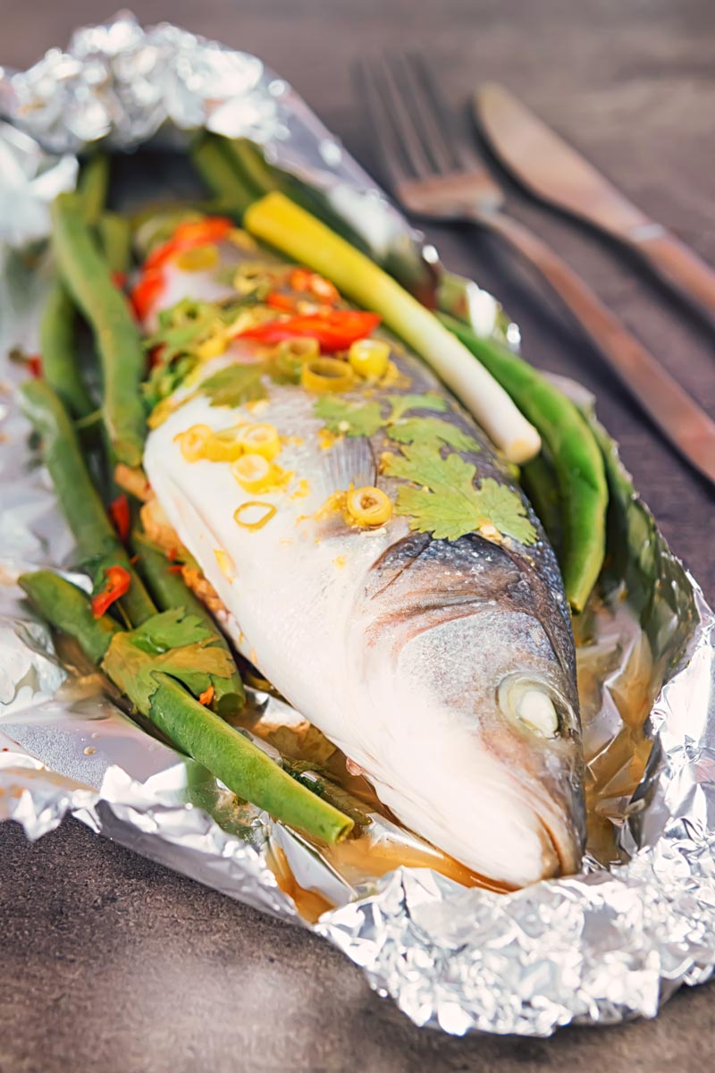Portrait image of a whole sea bass with vegetables served in foil a packet for fish en papillote