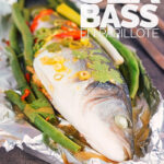 Portrait image of a whole sea bass with vegetables served in foil a packet for fish en papillote with text