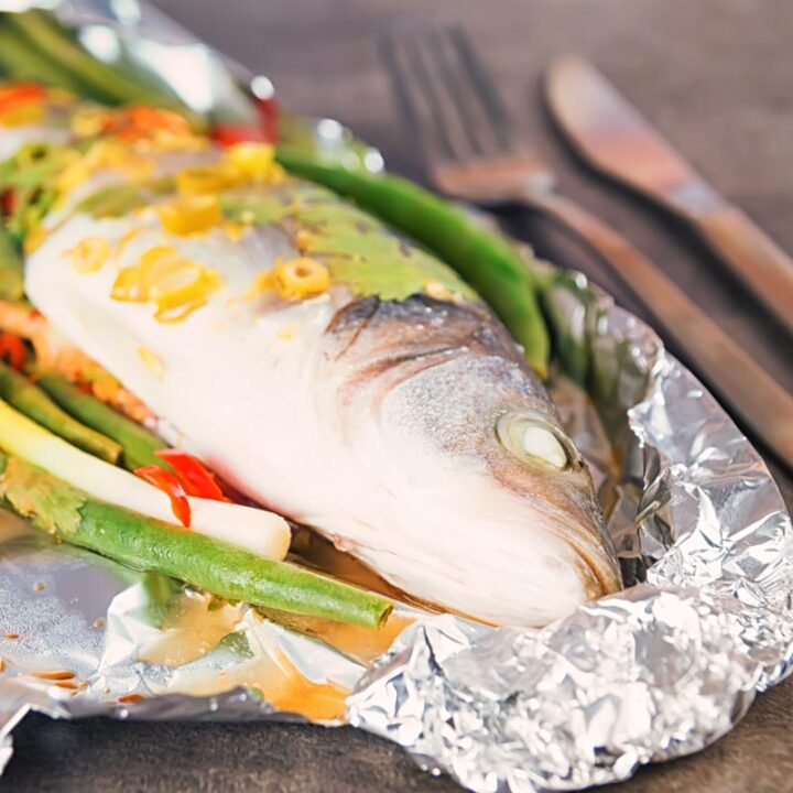 Square image of a whole sea bass with vegetables served in foil a packet for fish en papillote