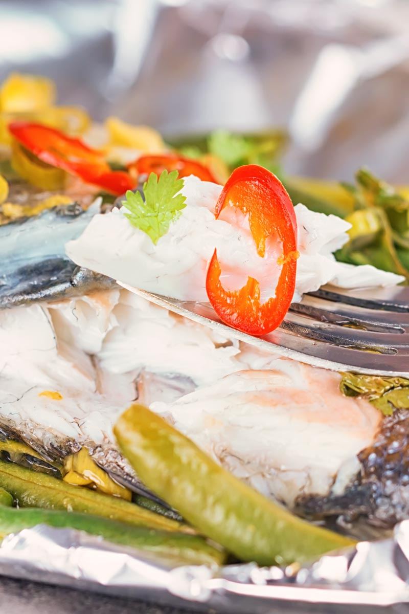 Portrait image of sea bass cooked in a foil packet en papillote showing the texture of the steamed fish