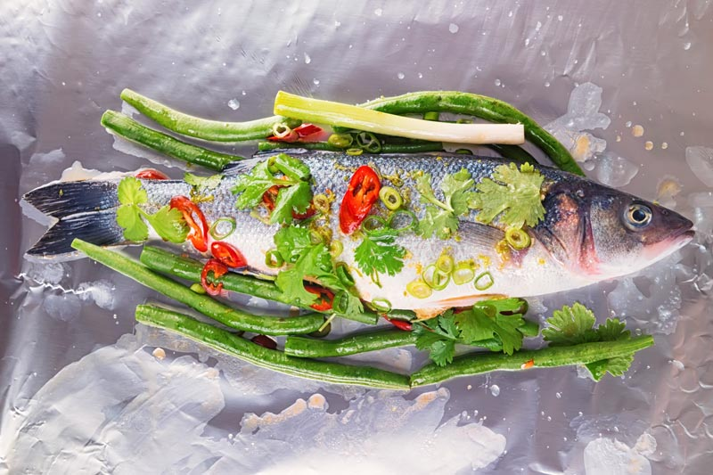 Landscape image of a raw whole sea bass with vegetables ready to be wrapped in a foil packet for fish en papillote