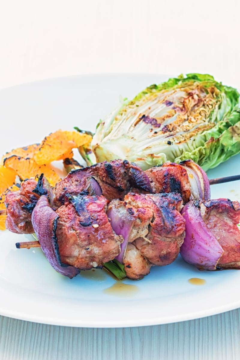 Portrait image of BBQ duck kebabs served on a white plate with grilled lettuce and seared orange segments