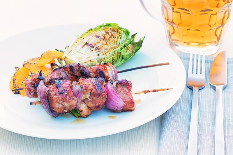 Landscape image of BBQ duck kebabs served on a white plate with grilled lettuce and seared orange segments served with a pint of beer