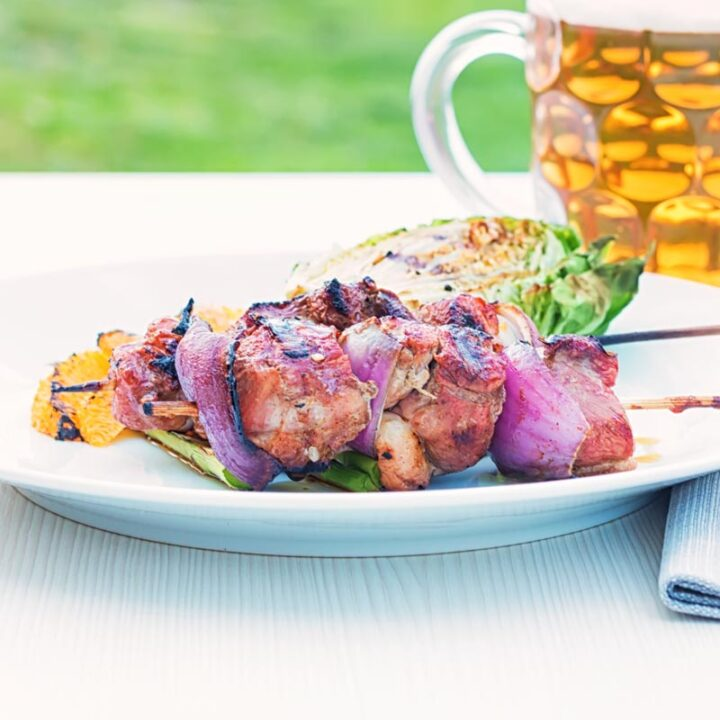 Square image of BBQ duck kebabs served on a white plate with grilled lettuce and seared orange segments served with a pint of beer