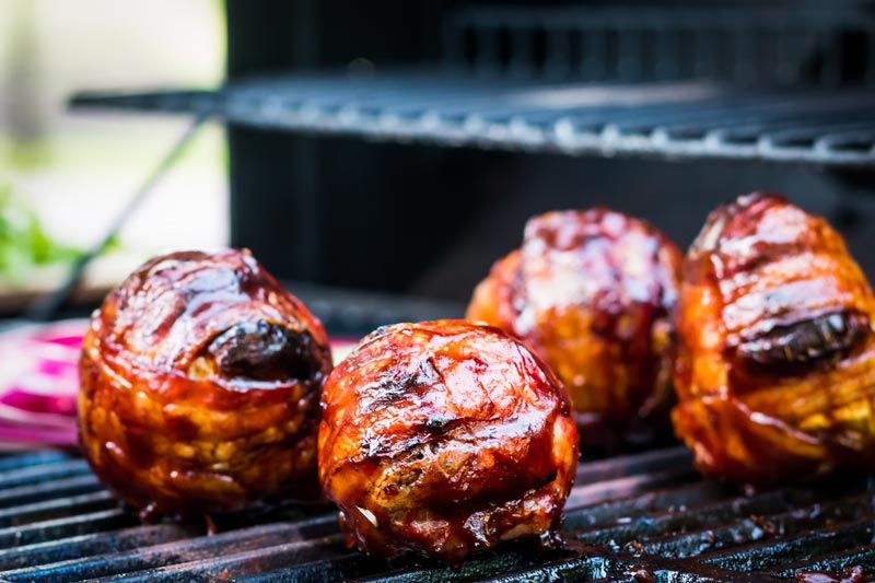 Landscape image of Bacon wrapped Grilled Stuffed Onions cooking on a grill