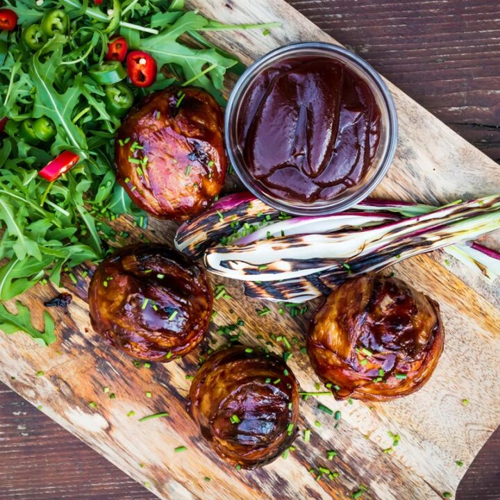 Square overhead image of Bacon wrapped Grilled Stuffed Onions served on a chopping board with BBQ sauce and a rocket salad