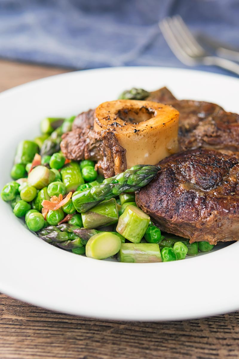 Portrait image of slowly braised beef shin on the bone served on a bed of peas, asparagus and bacon served in a white bowl