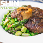 Portrait image of slowly braised beef shin on the bone served on a bed of peas, asparagus and bacon served in a white bowl with text