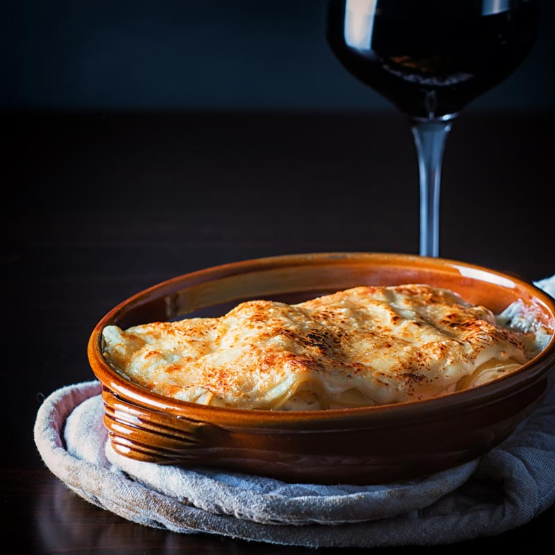 Square image of cauliflower cannelloni with a cheesy topping served in an earthenware bowl against a dark backdrop