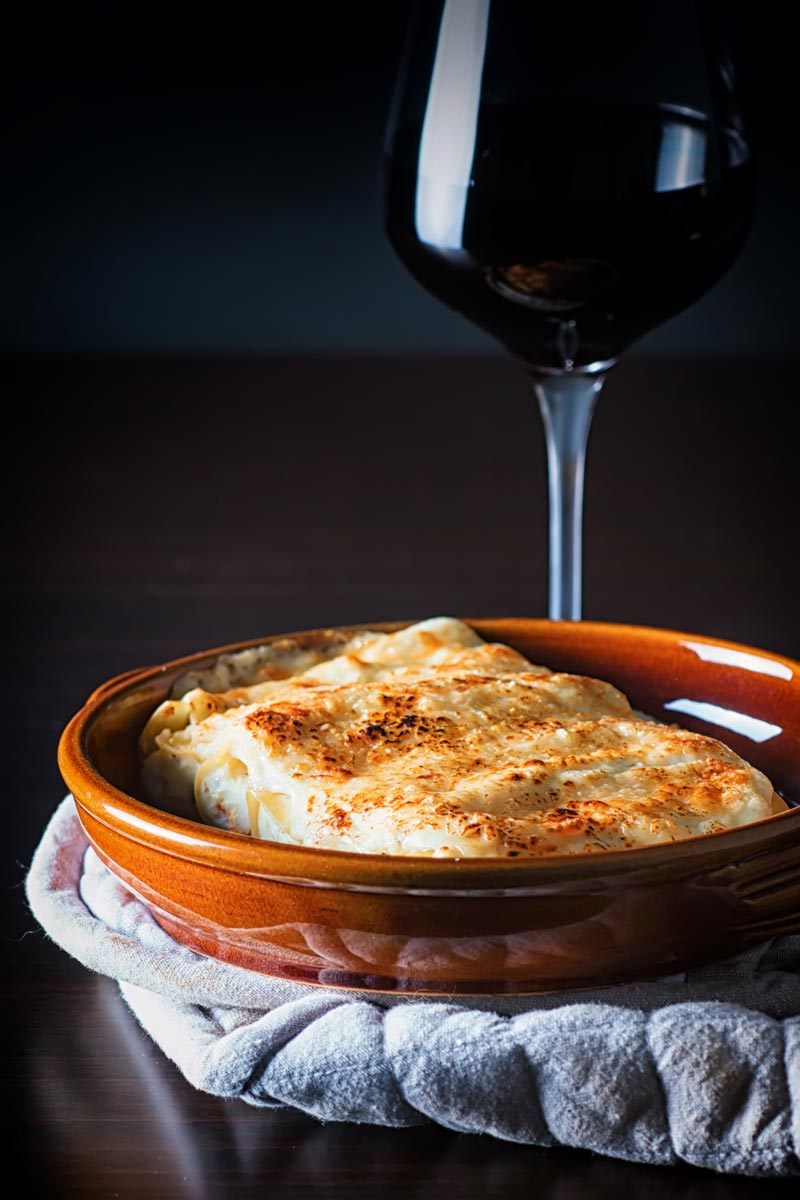 Portrait image of cauliflower cannelloni with a cheesy topping served in an earthenware bowl against a dark backdrop